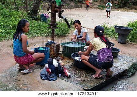 POPOTOTAN ISLAND PHILIPPINES - JANUARY 182012: Young women wash clothes in the Philippine village