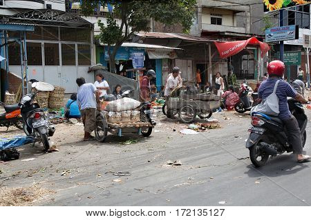 MEDAN INDONESIA - AUGUST 182012: People transported goods in motorcycle wagon
