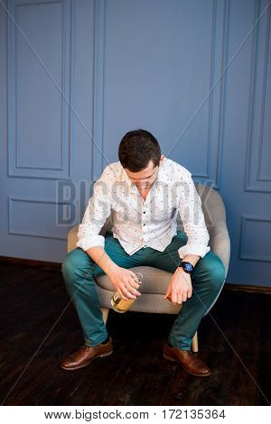 Lonely depressed man holding whiskey bottle and sitting in armchair. Man drinks whisky (alcohol)