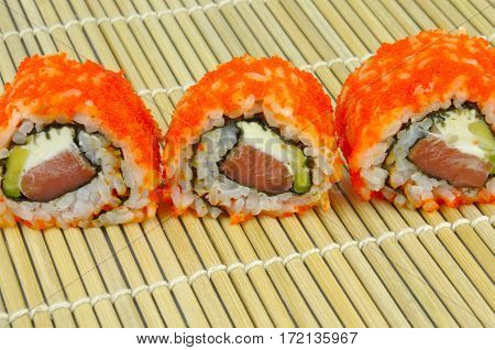 Sushi rolls with red masago roe, on bamboo mat