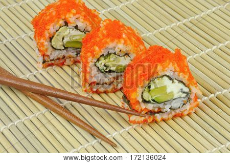 Sushi roll - avocado, cream cheese, omelette, masago roe - on bamboo mat with chopsticks