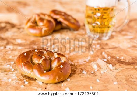Salty cooked pretzel and lager beer over the greaseproof paper