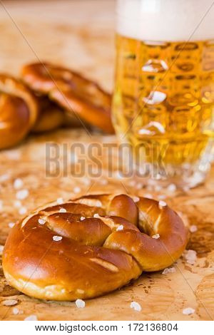 Closeup of salty cooked pretzel and lager beer over the greaseproof paper