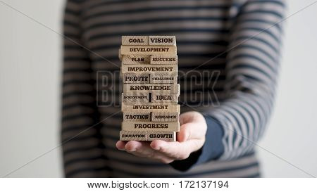 Man Holding Stack Of Wooden Bricks