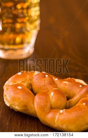Closeup of salty cooked pretzel and lager beer on a table