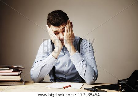 Very tired and depressed man at the office work. Low wages overtime working hours lack of career prospects concept. (Body language gestures psychology)