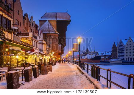 Medieval port crane at MotÅ?awa river in snowy Gdansk, Poland