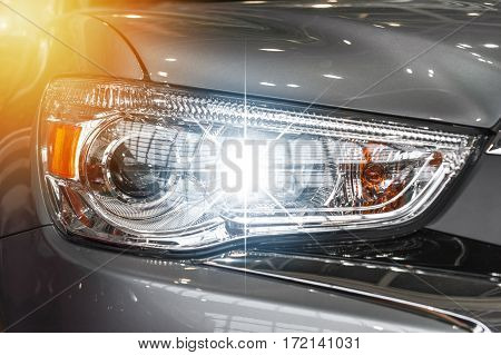 Closeup on an headlight of a grey sport car in the sunlight