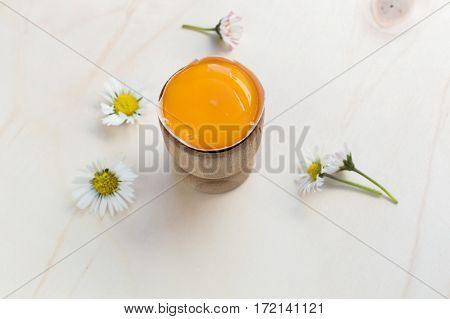 Fresh organic yolk and some daisies on a wooden surface