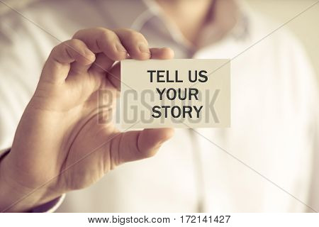 Businessman Holding Tell Us Your Story Message Card