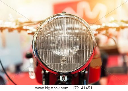 Headlight of a powerful vintage motorbike in the sunlight