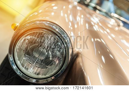 Closeup on headlight of a vintage car in the sunlight