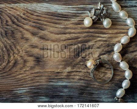 Luxury pearl necklace, ring and pearl earrings on old wooden table. with copy space, close up.