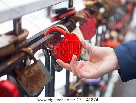Female Hand Holds Old Closed Red Padlock In Heart Shape On A Blurred Background. Close Up.