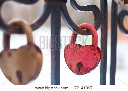 Vintage Closed Gold And Red Padlocks In Heart Shape Close Up On A Blurred Background.