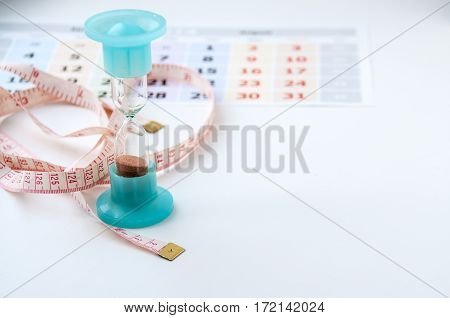 Hourglass, White Centimeter And The Calendar On A Light Background