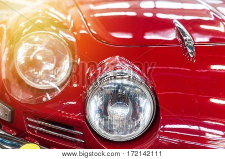 Closeup on headlight of a red car in the sunlight