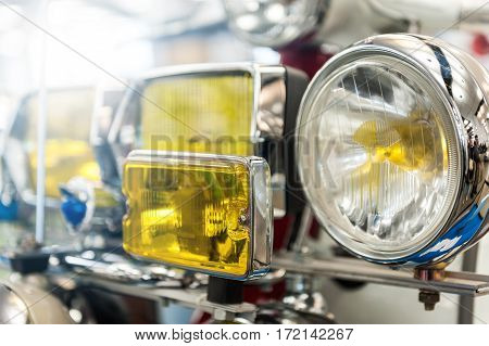 Many headlights of a powerful vintage motorbike in the sunlight