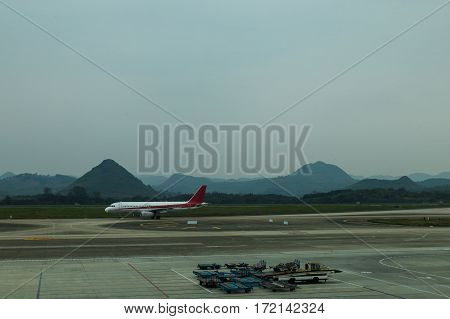 airplane landing to Chongqing airport runway in China with cloudy mountain background