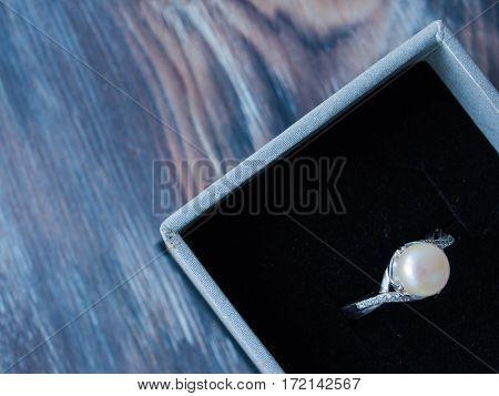 Elegant pearl ring in black box on white background