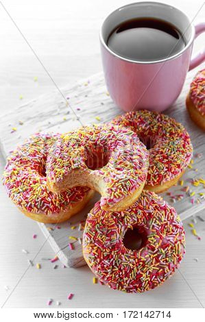Iced doughnut rings with rainbow sparkl strands and cup of coffee, tea.