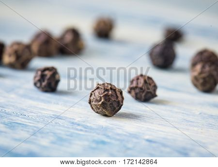 Black pepper peas. Macro close-up. Blue wood background.