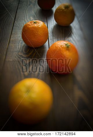 Fresh oranges on a brown wooden background