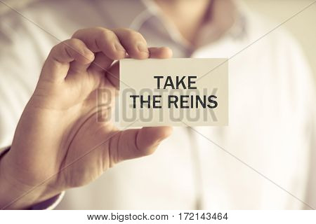 Businessman Holding Take The Reins Message Card