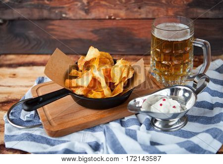 Crackling Tasty Snack From Potato Chips And Spicy Dip And Glass Of Cold Beer On A Wooden Background
