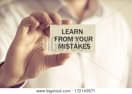Businessman Holding Learn From Your Mistakes Message Card