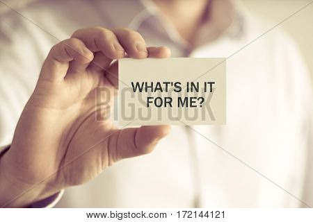 Businessman Holding Whats In It For Me ? Message Card