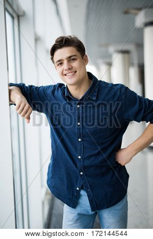 Handsome man with arms crossed looking out of the window
