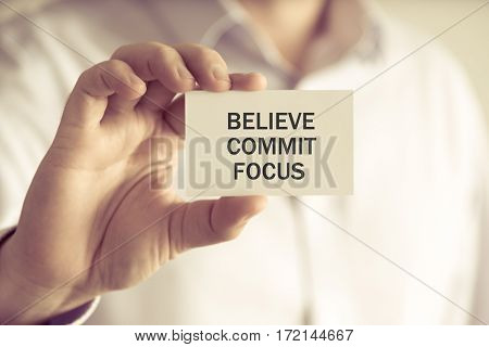 Businessman Holding Believe, Commit, Focus Message Card