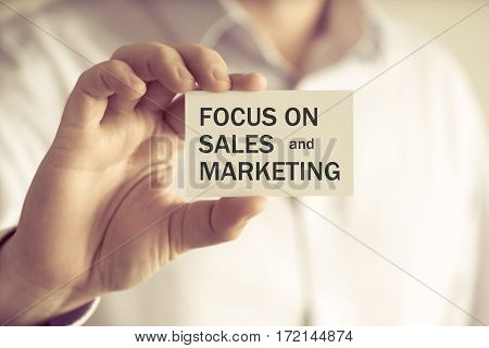 Businessman Holding Focus On Sales And Marketing Message Card