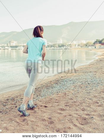Unrecognizable young woman running on sand beach near the sea in summer