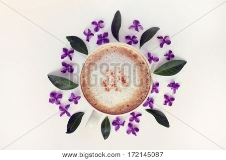 flat layout of frothy cappuccino and a floral pattern desk top view / table setting with aroma of spring