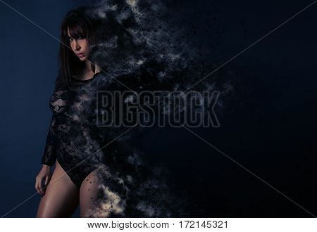 Young woman in lingerie creating a particle dispersion effect over a gray background