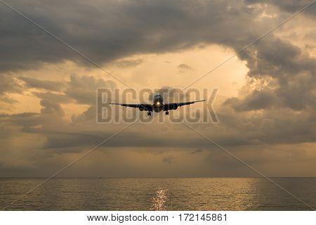 Landscape of sunset with Plane from Phuket at Nai Yang Beach Phuket Province Thailand.
