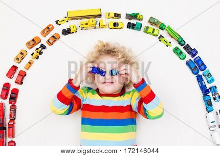 Funny curly toddler boy playing with his model car collection on the floor. Transportation and rescue toys for children. Rainbow toy mess in kids room. View from above. Many cars for little boys.