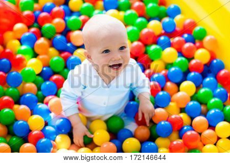 Child Playing In Ball Pit On Indoor Playground