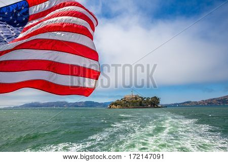 Alcatraz island in San Francisco Bay skyline, California, United States. Sea view from boat to Alcatraz with American flag waving. Freedom and travel concept. Icon and landmark of San Francisco.
