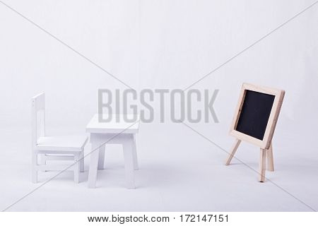 White wooden chair and desk with a blackboard in classroom