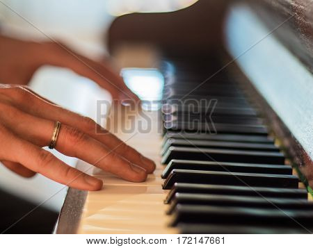 Man hands playing the piano. Close up.