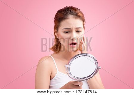 Pretty young asian woman holding a mirror touch and worrying about her face