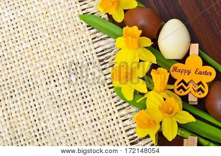 Easter decoration fresh spring narcissus flowers and chocolate eggs.