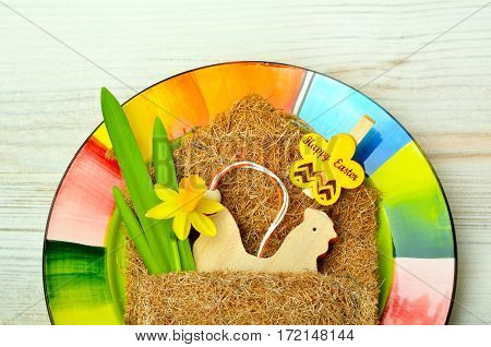 Easter decoration and fresh spring narcissus flowers on colored plate.