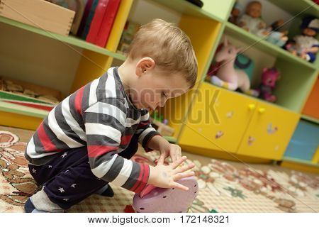 Сhild playing with a toy in kindergarten