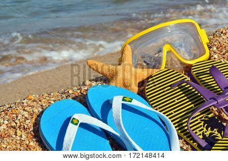 Colorful flip flops starfish and underwater mask on the beach.