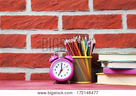 Colorful books with pencils and alarm clock on a brick wall background