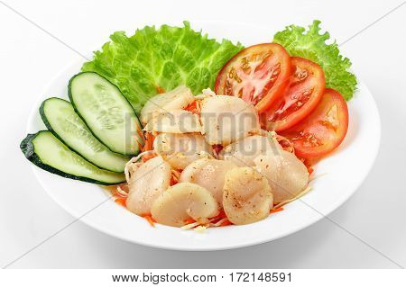 Fried scallops in garlic sauce, lettuce, cucumber and tomatoes on a white plate on a white background